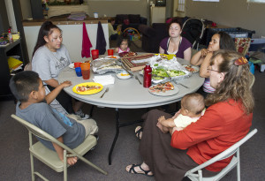 The families pray before sharing a meal.
