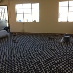 Macadam employee is putting the finishing touches on the carpet in the upstairs living room.
