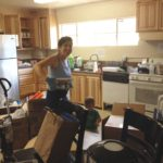 Lisa is washing dishes and putting them in the new cupboards. They got all dusty in the construction!