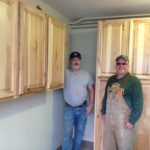 Dan and Bill finished installing the kitchen cabinets and added these to the Laundry room. How each family has a cupboard to store their food and there is one left over for household supplies.