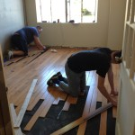 Workers from Macadam Floor & Design are laying the new floors with material donated through the Home Builders Foundation.