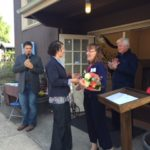 Stephanie VanReen, president of the board of Community of Hope, gives Linda Jo flowers and chocolate.
