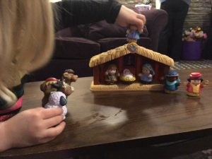 Child playing with Nativity set